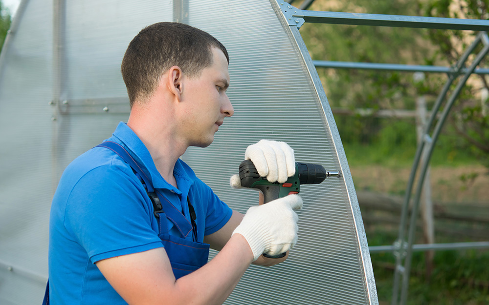 Man using drill to attach greenhouse panels.