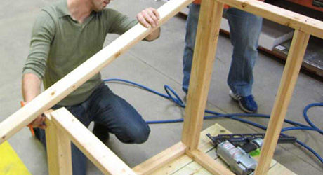A person constructing the siding of a dog house