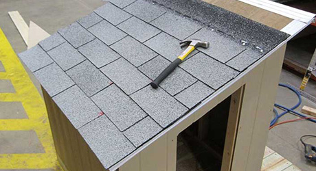 Shingles and a hammer on the roof of a dog house