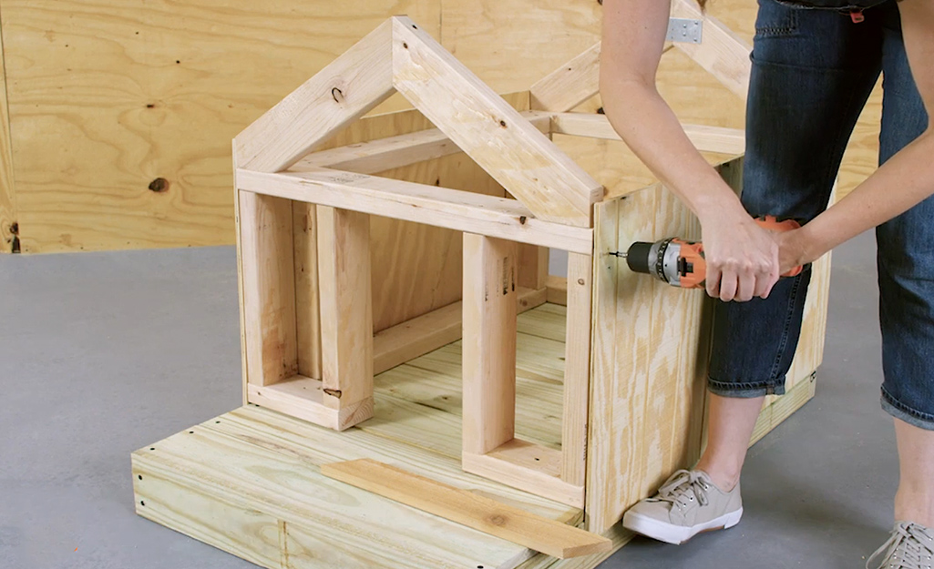A worker drills walls onto the dog house frame.
