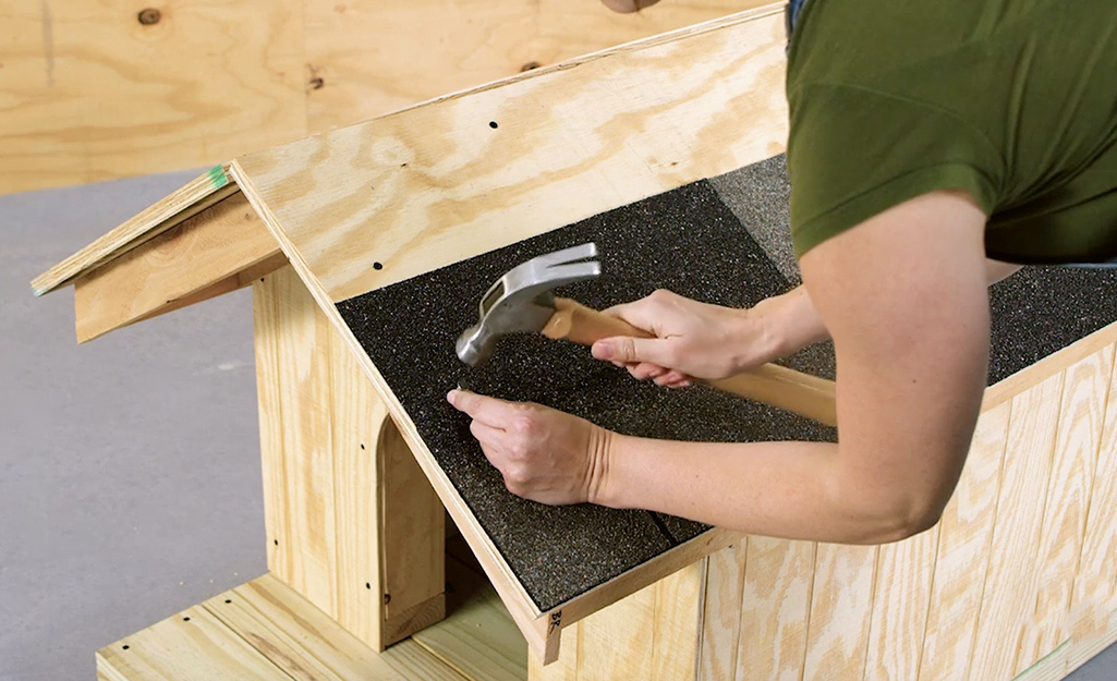 A worker nails shingles to the roof of the dog house.