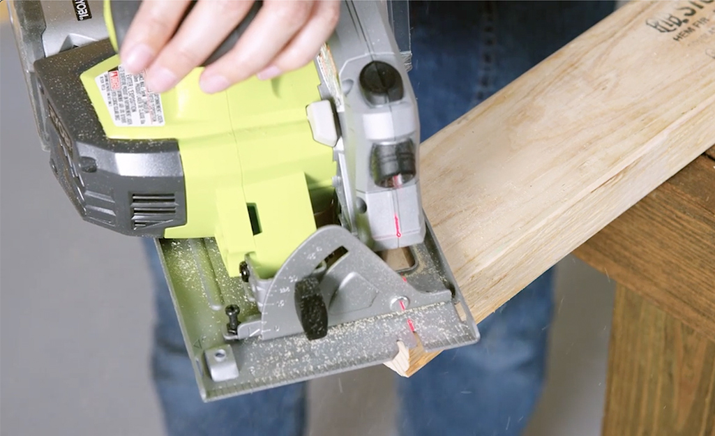 A close-up image of a saw making angled cuts to a stud.