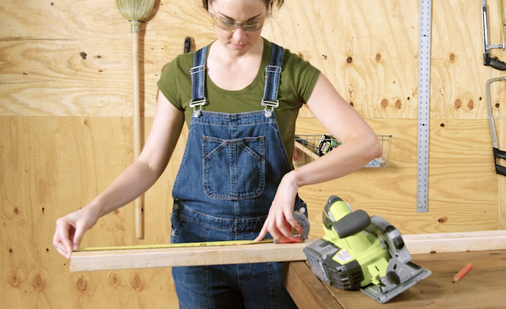A worker measures studs for the dog house.