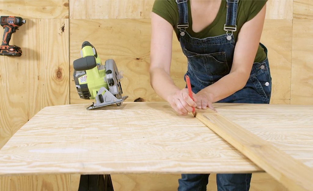 A worker draws lines on plywood for a dog house wall.