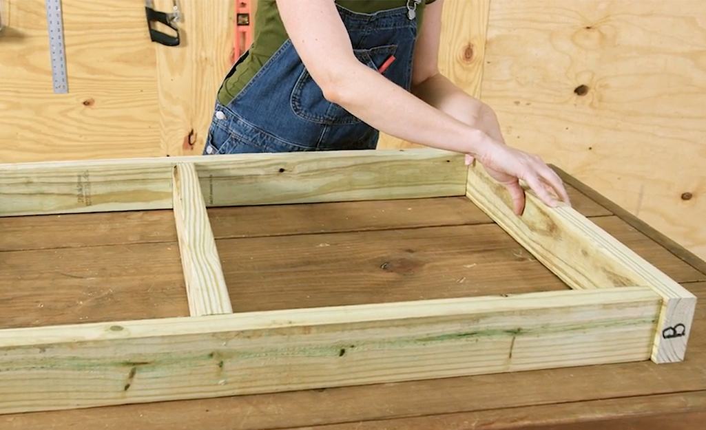 A worker works on the floor frame of the dog house.