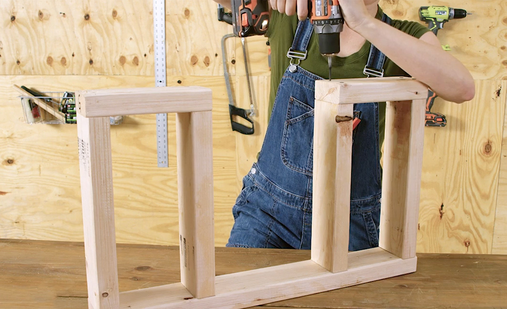 A worker assembles the doorway for the dog house.