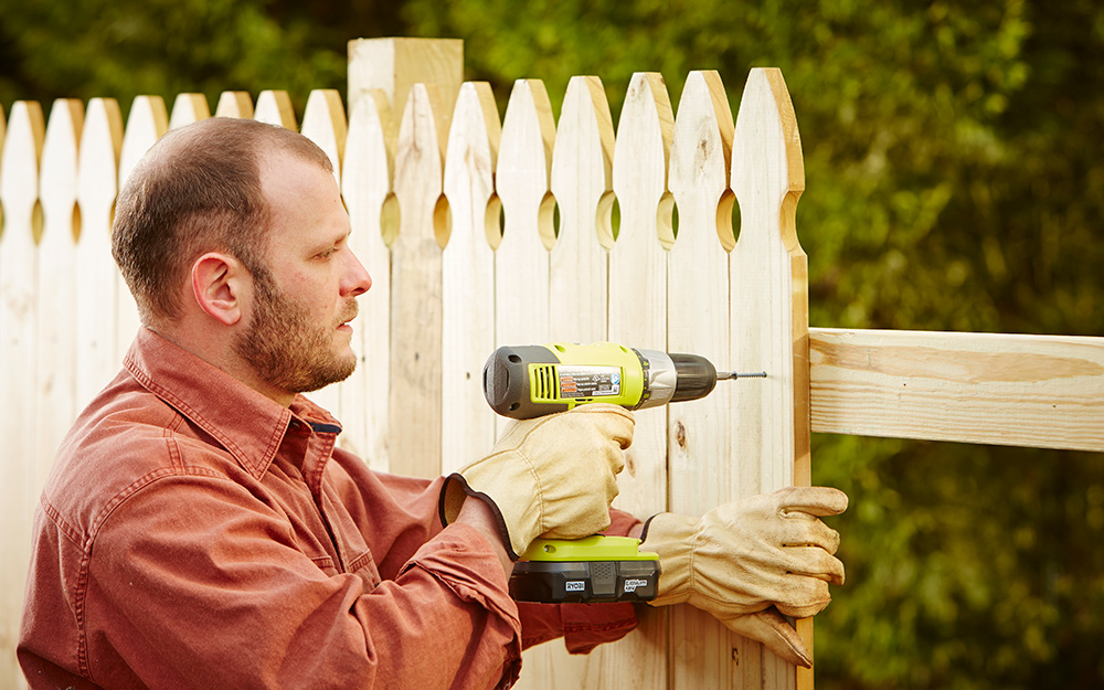 A person uses a power drill to attach fence pickets to a rail.