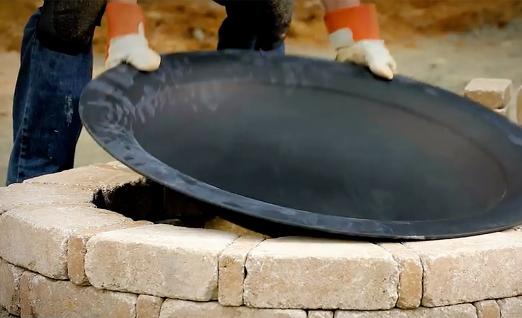 A person placing a fire pit bowl on a fit pit.