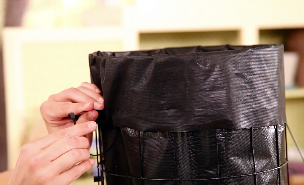 Một người buộc vải phong cảnh xung quanh khung dây bằng dây buộc zip.