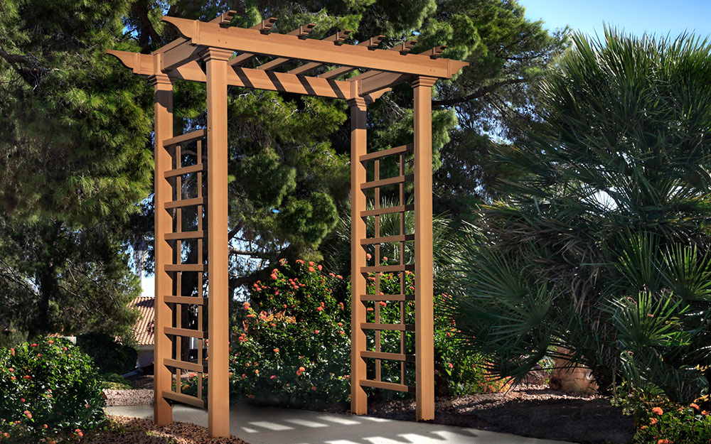A wooden garden arbor with trellis sides spans the walkway into a garden.