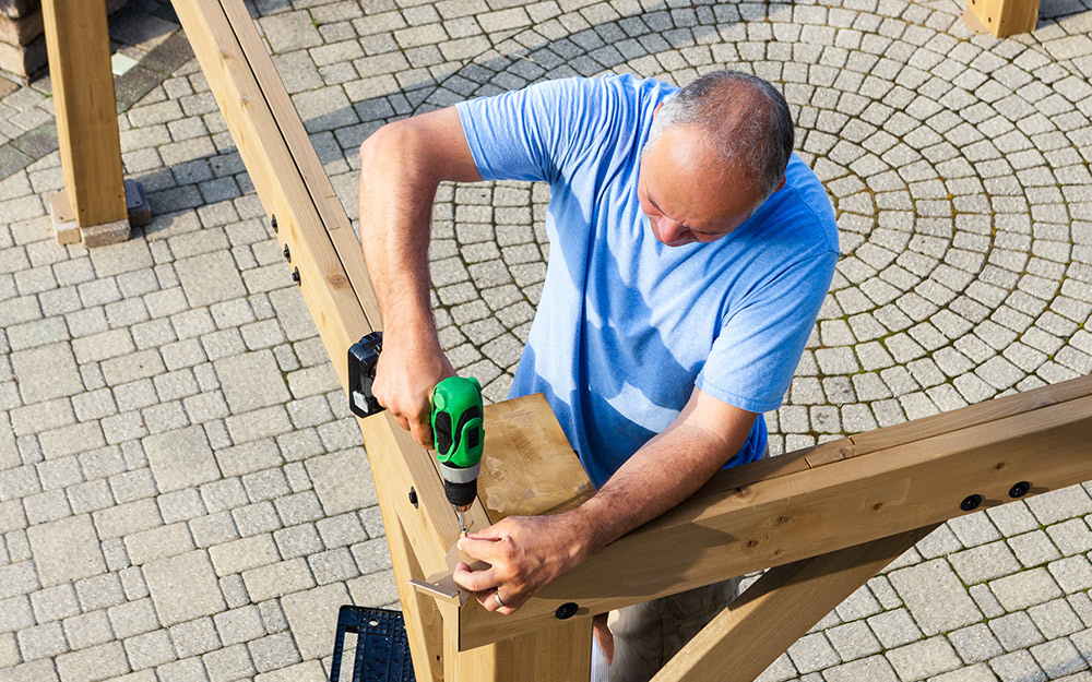 A person uses a drill to secure the wood parts of an arbor.