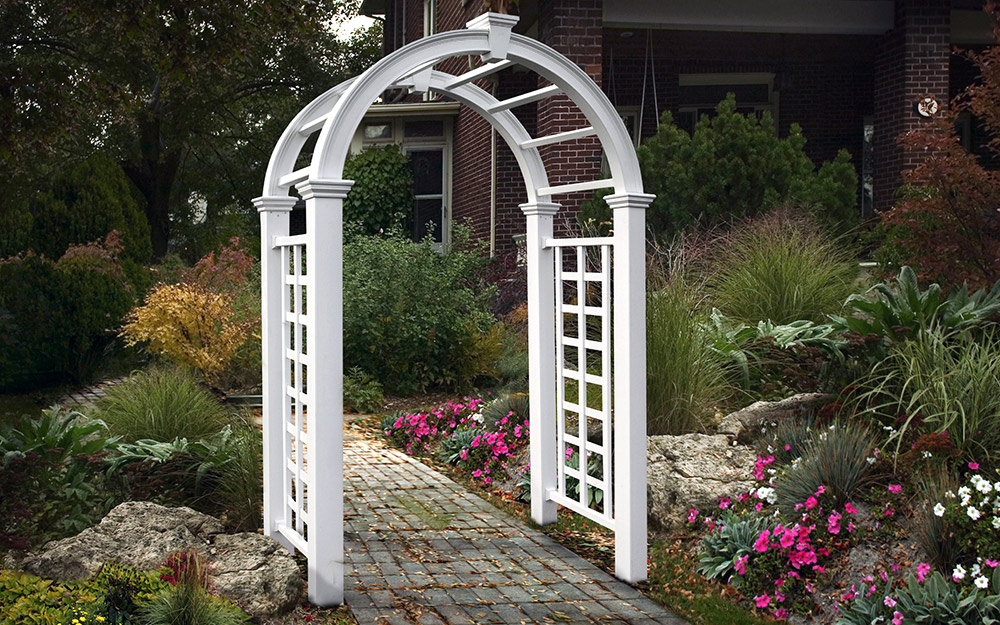 A white arched garden arbor with lattice on its sides spans a walkway.