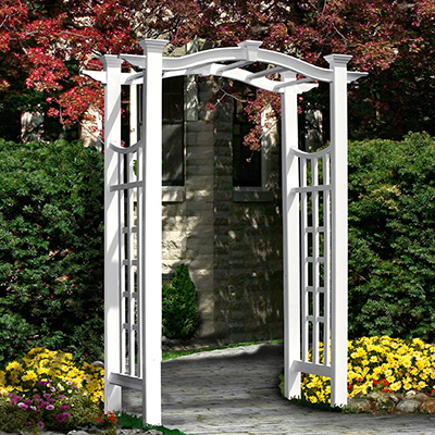 A white garden arbor with a trellis on its sides spans a walkway.