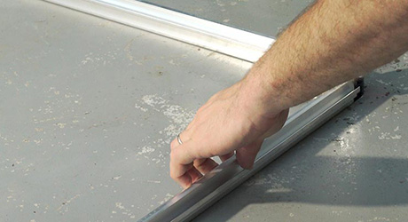 A person assembling the base and corner uprights of a greenhouse.