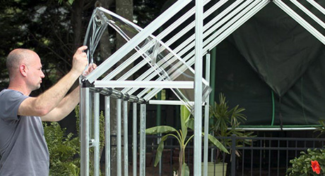 Person installing greenhouse wall panels.
