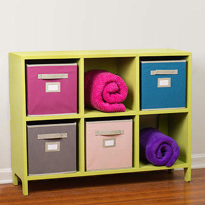 A kids cubby storage unit with added cloth bins and blankets.
