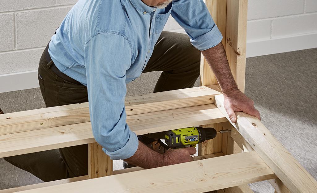 Người đàn ông đang lắp ráp các tấm gỗ.