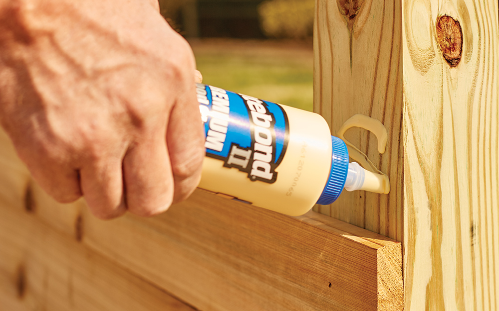 person using wood glue on a wooden frame