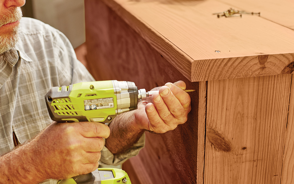 person drilling into the side of a wooden cabinet