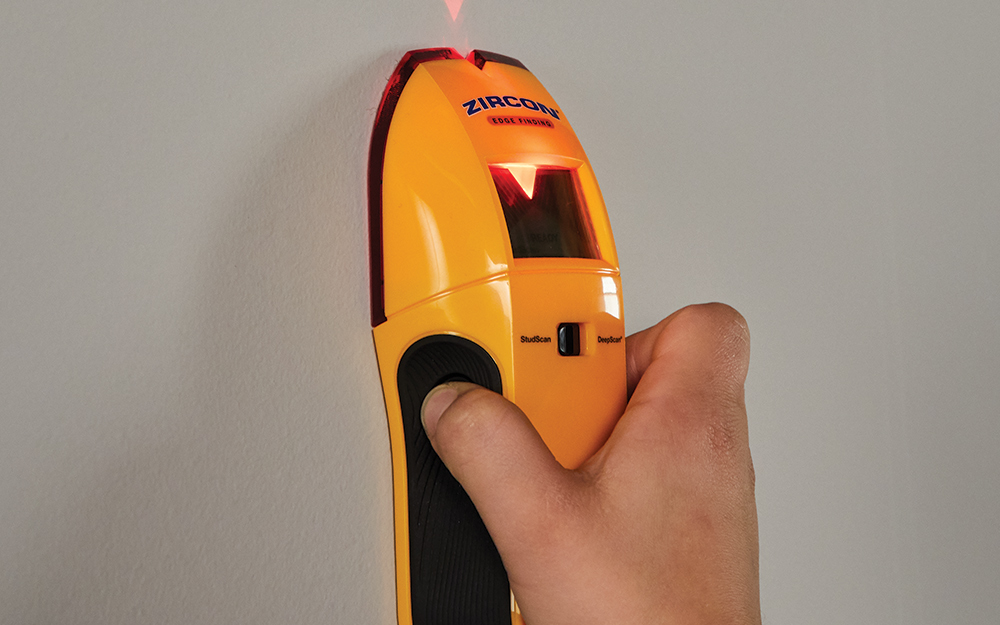 person using a stud finder on a blank wall