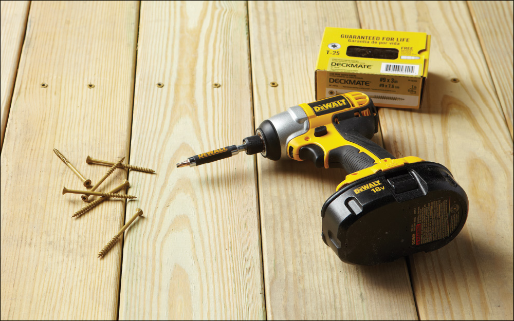 a power drill lying next to a bunch of screws