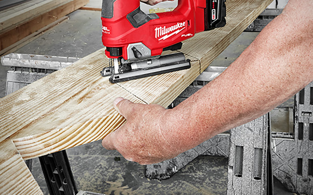man rounding the edges of a wooden board using a power saw