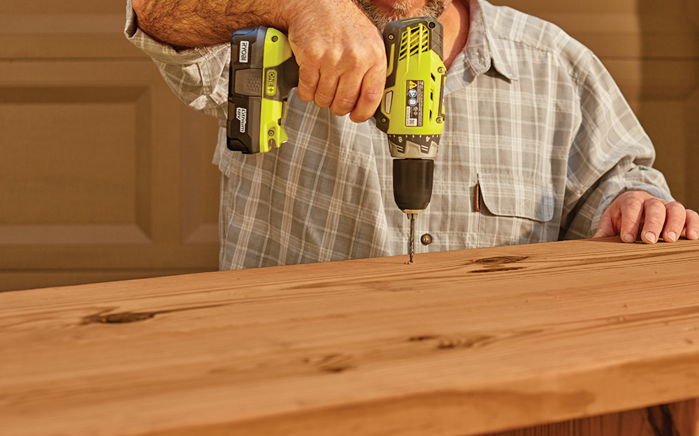 man drilling holes in a wooden frame