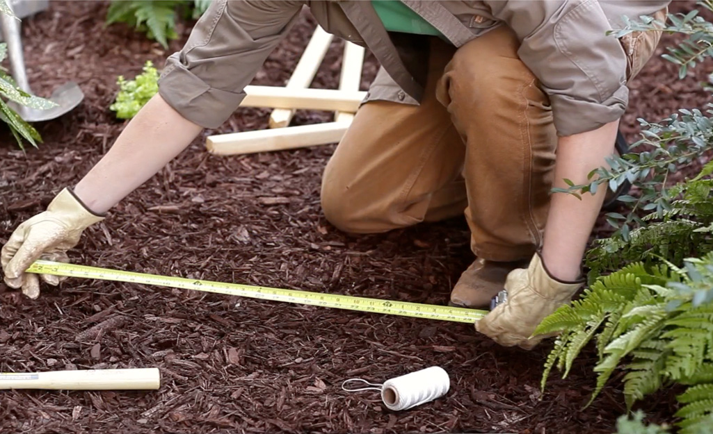 A person measures an area of landscape for a paver path project.