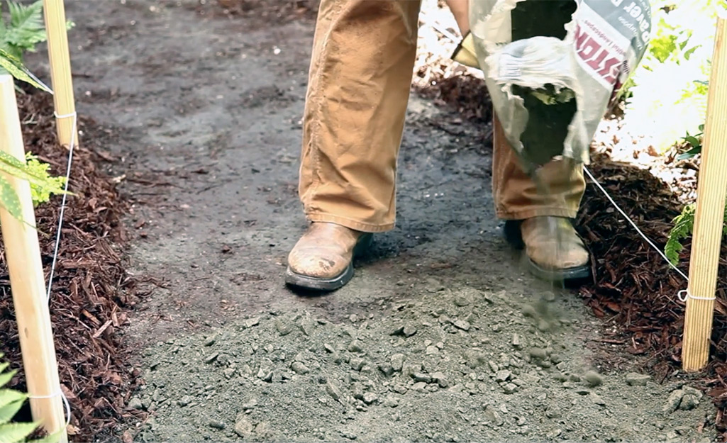 A person spreads paver base.