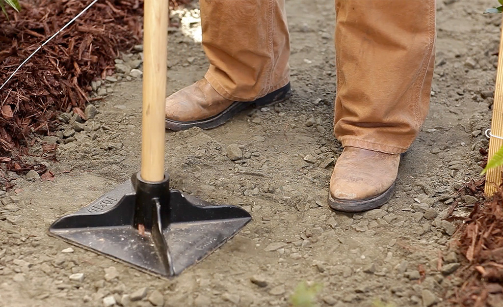 A person using a tamper to even out leveling sand in a paver path project.