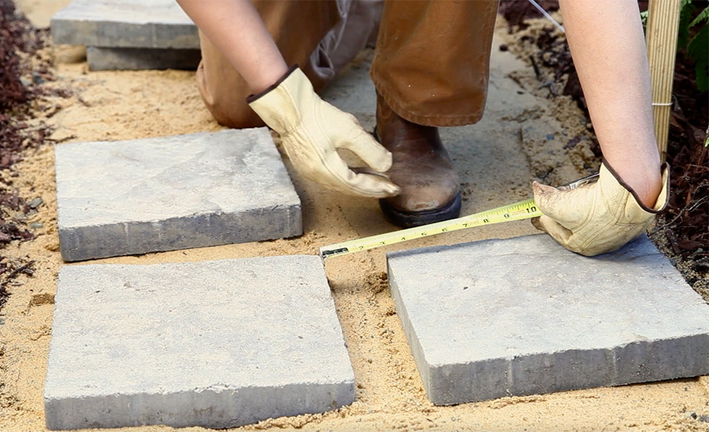 A person laying out paver stones.