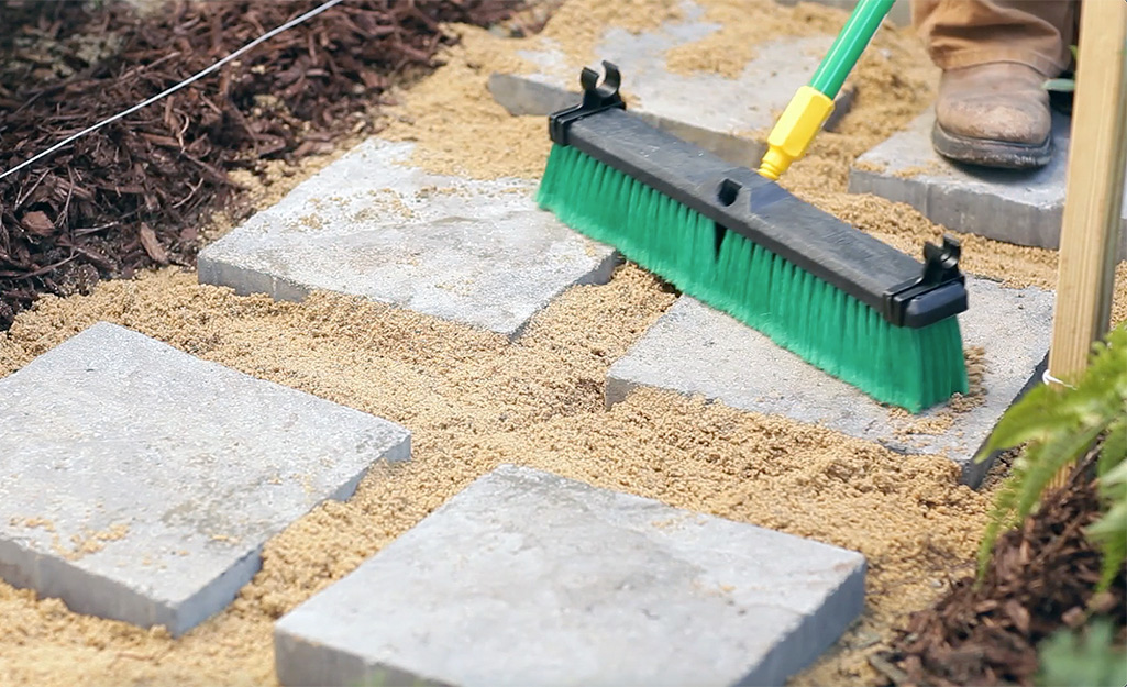 A person brushing paver sand between paver stones.