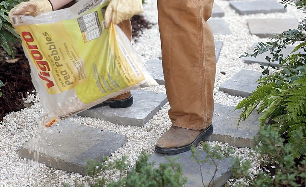 A person filling in space between paver stones with pea pebbles.