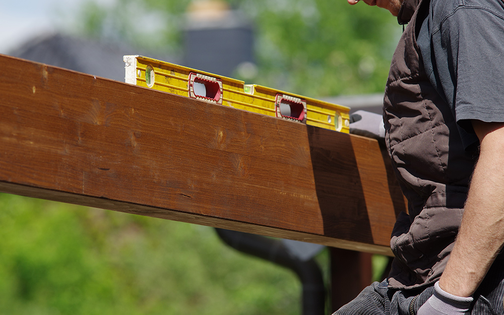 A man checking the level of a a crossbeam.