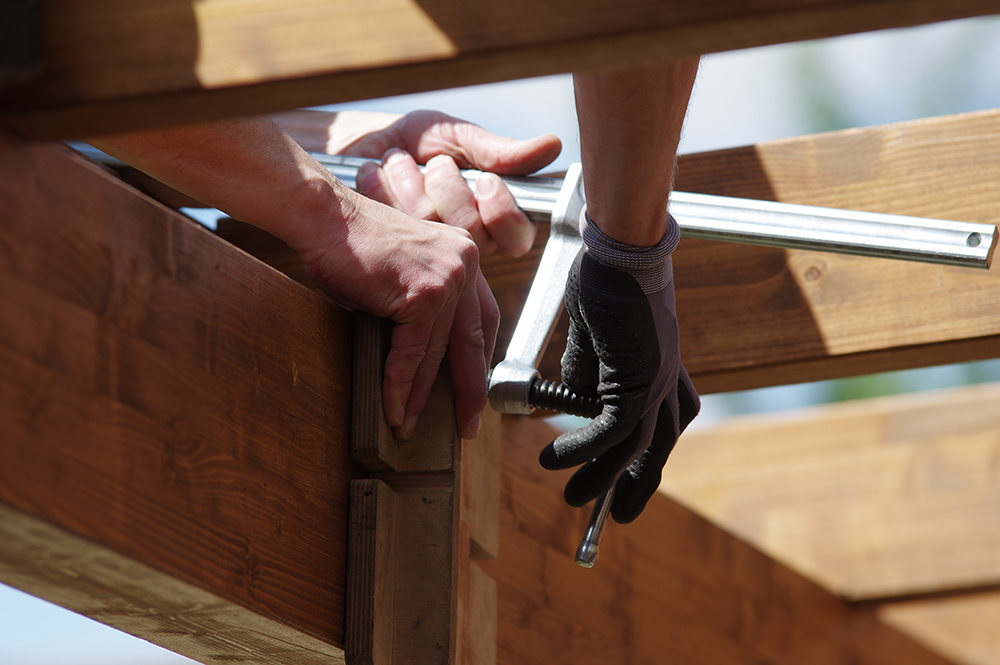 A person installing a rafter.