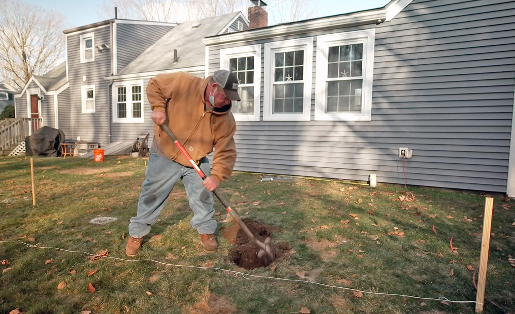A person digging a hole for a deck footing.