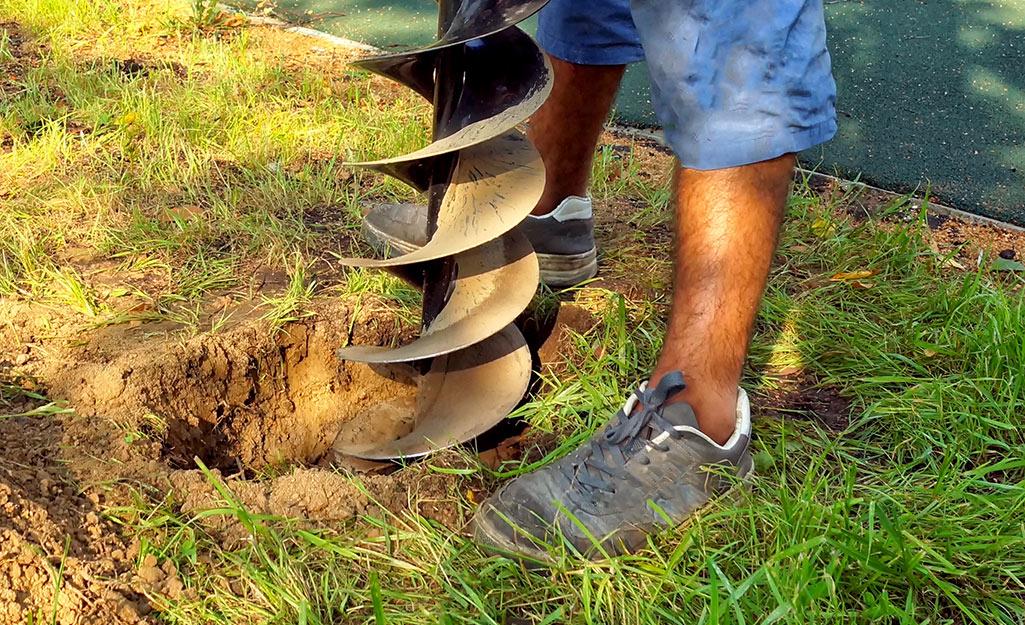 A man digs holes in a backyard.