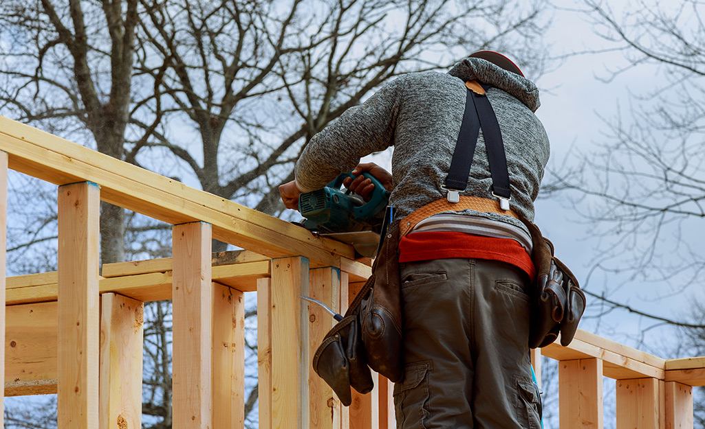A man wearing safety gear attaches beams.