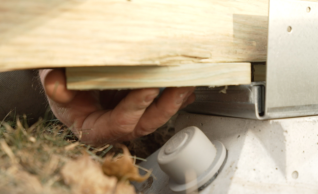 A person shimming a deck beam to sit level in a post cap.