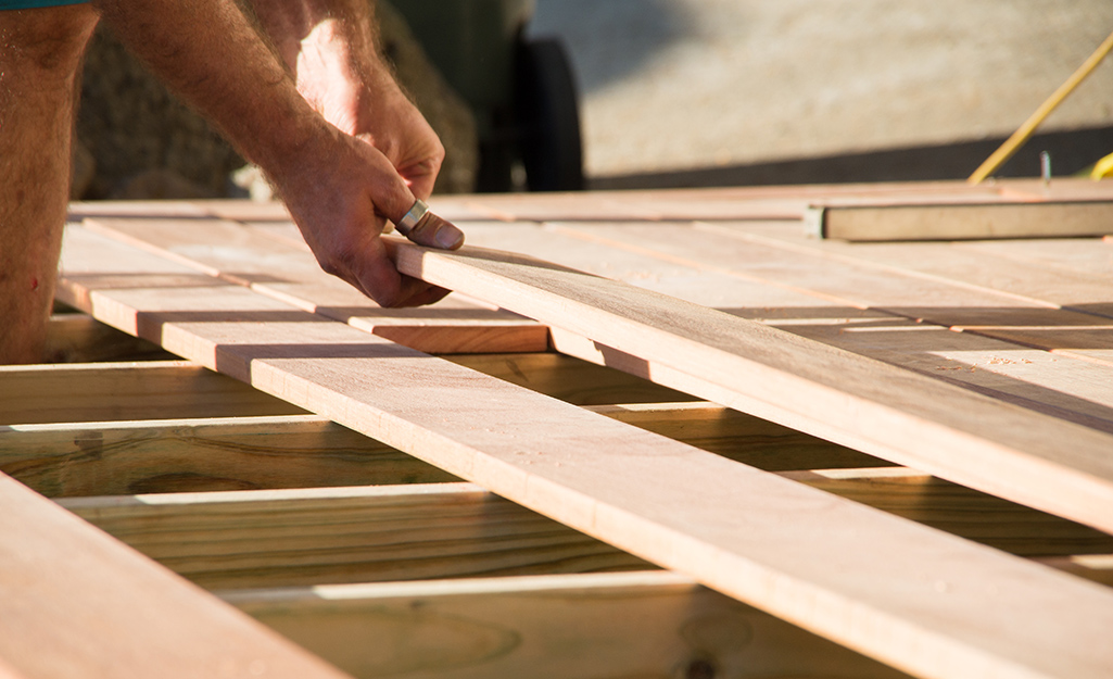 A person installing decking boards.