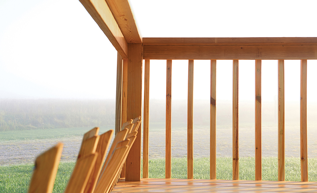 A raised deck with railings almost completely installed.
