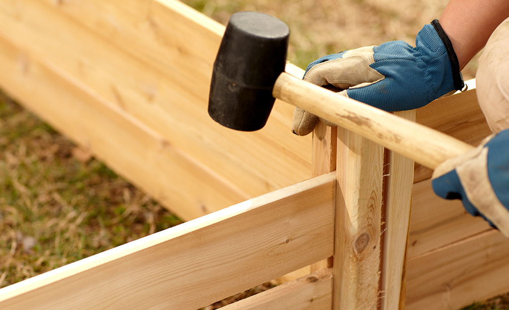 Someone hammering a raised garden bed using a rubber mallet.