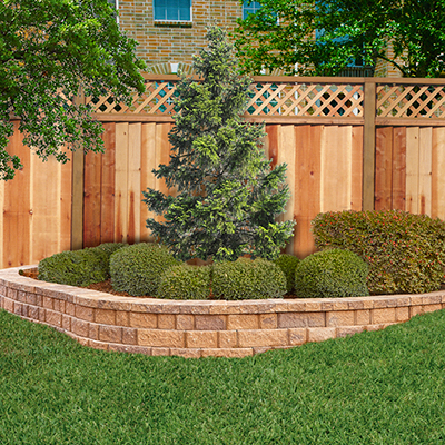 a retaining wall in a yard with healthy grass and shrubs