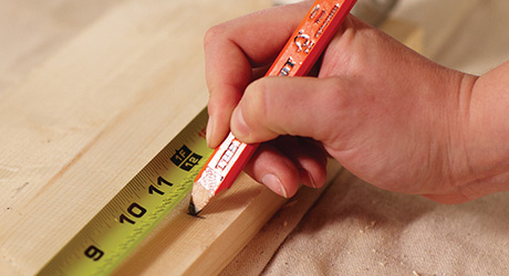 Một người đo ván gỗ và đánh dấu nó bằng bút chì.