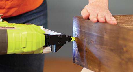Một người dùng súng bắn đinh để đóng đinh vào góc hộp gỗ.