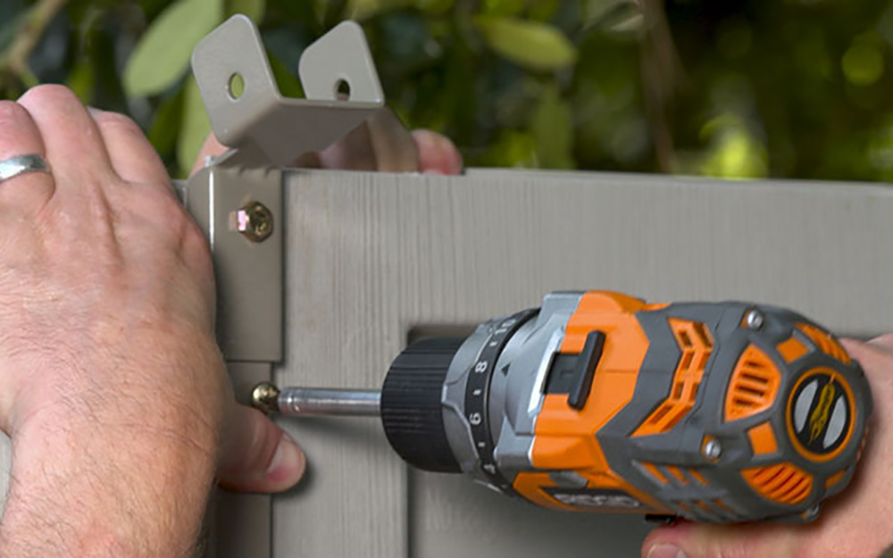 A man screws in the shelf support for a DIY shed.