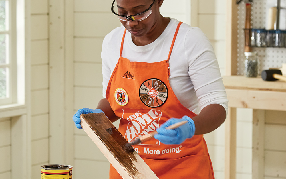 Woman stains wood for tote with wood stain.