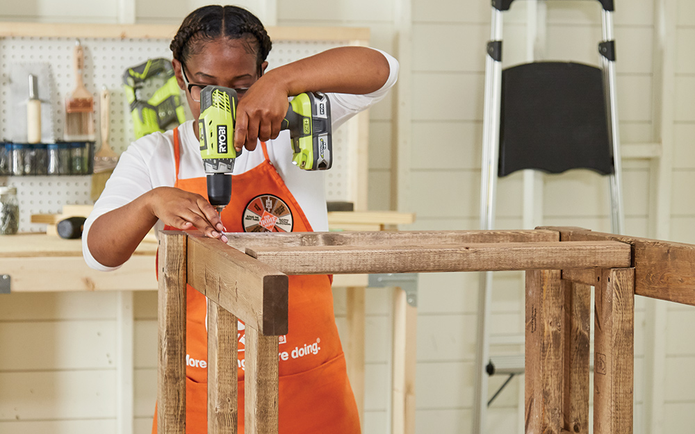Woman attaches sides together with drill and screws.