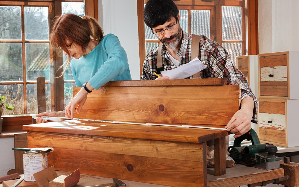 two people measuring wood to build a staircase
