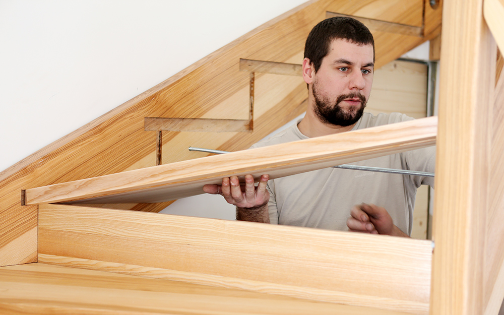 a man installing a tread on a new staircase